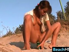 petite-teen-riding-a-bottle-at-the-beach
