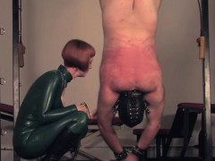 Dominating redhead flogging sub in a bodysuit